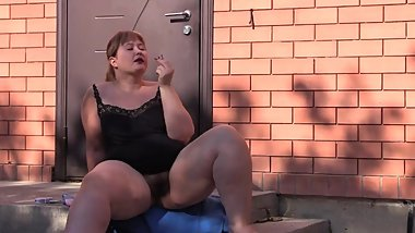 BBW with a hairy pussy without panties sits on a porch, smokes a cigarette. Amateur fetish outdoor.